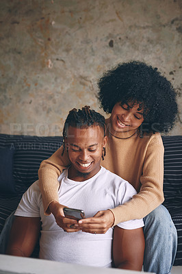 Buy stock photo Shot of a young couple using a cellphone together at home