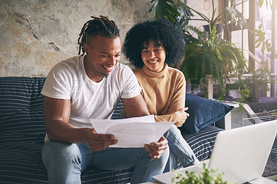 Buy stock photo Shot of a young couple going through paperwork while using a laptop together at home