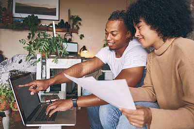 Buy stock photo Shot of a young couple using a laptop while going through paperwork together at home