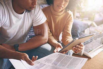 Buy stock photo Shot of a young couple using a digital tablet while going through paperwork together at home
