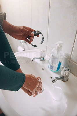 Buy stock photo Closeup shot of an unrecognisable woman washing her hands while being timed with a watch in a bathroom at home