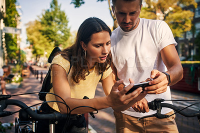 Buy stock photo Shot of a young couple using a smartphone while exploring the city of Amsterdam by bike