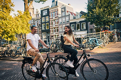 Buy stock photo Shot of a young couple exploring the city of Amsterdam by bike