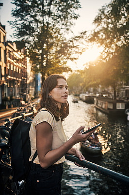 Buy stock photo Shot of a young woman using a smartphone while exploring the city of Amsterdam