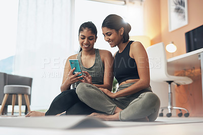 Buy stock photo Shot of two young women looking at something on a cellphone while sitting at home in exercise clothes