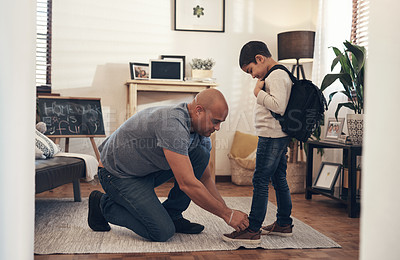 Buy stock photo Shot of an adorable little boy getting his shoelaces tied by his father before leaving to go to school