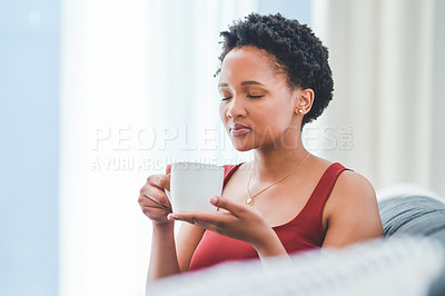 Buy stock photo Cropped shot of a young lady enjoying a cup of tea on the couch in her apartment
