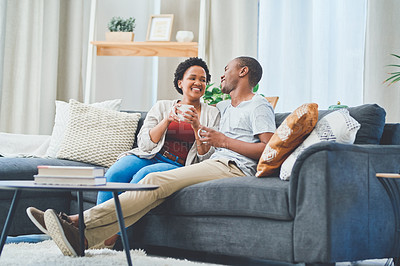 Buy stock photo Shot of a young couple laughing together sitting on the couch in their apartment while she enjoys a cup of coffee