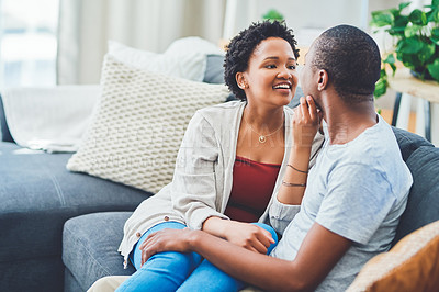 Buy stock photo Cropped shot of a young loving couple looking endearingly at each other  while she caresses his face on the couch in their apartment