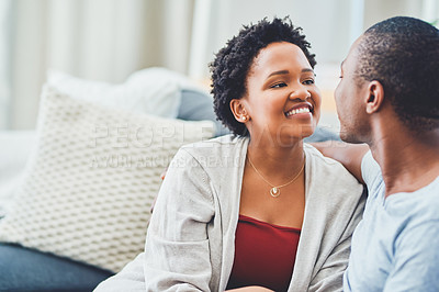 Buy stock photo Cropped shot of a young loving couple looking endearingly at each other in their apartment while sitting on the couch