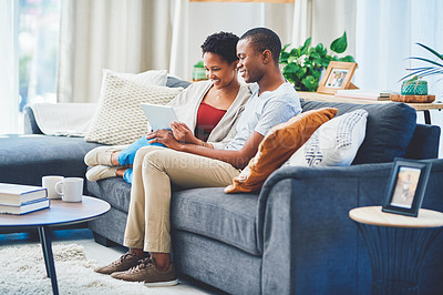Buy stock photo Shot of a young loving couple browsing on a tablet together while holding hands sitting on the couch in their apartment