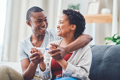 Buy stock photo Cropped shot of a smiling young couple holding hands as she holds a positive pregnancy test while sitting on the couch in their apartment