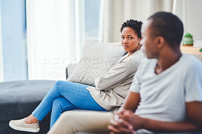 Buy stock photo Cropped shot of a young couple sitting apart on a couch after an argument while they look at each other in disdain