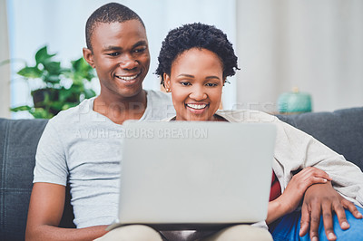 Buy stock photo Cropped shot of a smiling young loving couple embracing and browsing on a laptop together while sitting on the couch in their apartment
