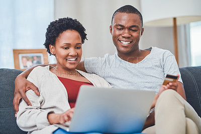 Buy stock photo Cropped shot of a smiling young couple making an online purchase while sitting on the couch together in their apartment