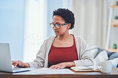 Buy stock photo Cropped shot of a young lady reviewing work on her laptop while working from home at her desk