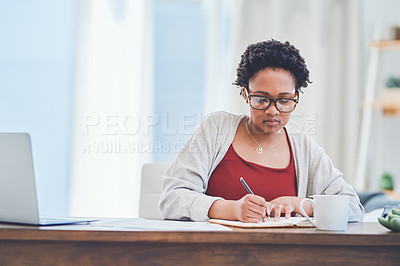 Buy stock photo Cropped shot of a young lady making notes on a notepad while working from home at her desk