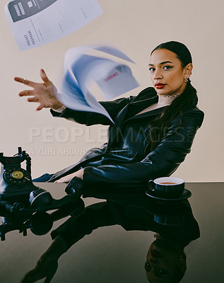Buy stock photo Studio portrait of a beautiful young woman throwing paperwork in the air while sitting at a table against a brown background