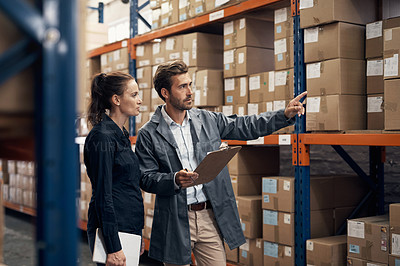 Buy stock photo Shot of a young man and woman working together in a warehouse