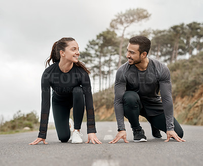 Buy stock photo Full length shot of two young athletes crouched down in a starters position before exercising outside