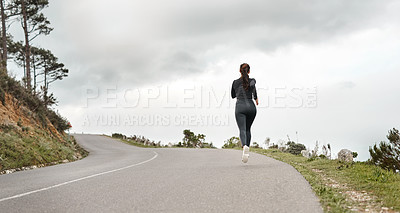 Buy stock photo Full length shot of an unrecognizable woman jogging alone outdoors
