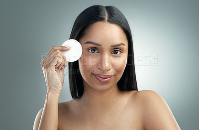 Buy stock photo Shot of a beautiful young woman holding a cotton pad against her face