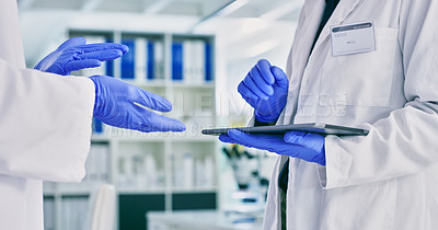 Buy stock photo Closeup shot of two unrecognisable scientists having a discussion while using a digital tablet together in a lab