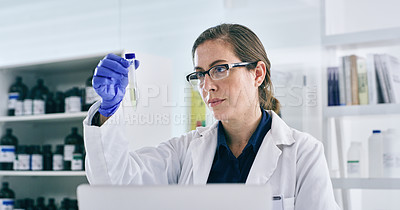 Buy stock photo Shot of a young woman analysing samples while working on a laptop in a lab