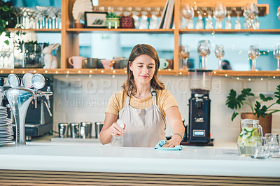 Buy stock photo Shot of a young woman sterilising a counter while working in a cafe