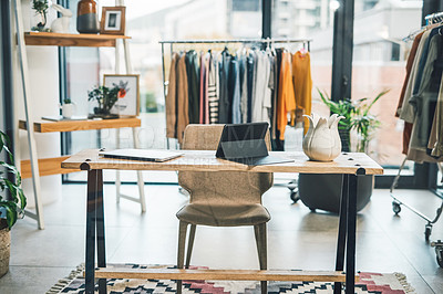 Buy stock photo Shot of an empty clothing boutique with wireless technology on a desk