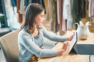 Buy stock photo Shot of a young woman using a digital tablet and smartphone while working in a boutique