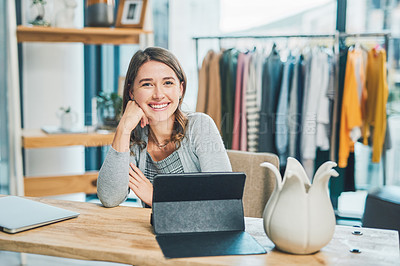 Buy stock photo Portrait of a young woman using a digital tablet and smartphone while working in a boutique