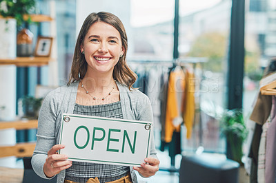 Buy stock photo Portrait of a young woman holding up an open sign in her boutique