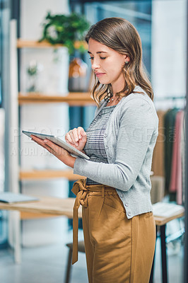 Buy stock photo Shot of a young woman using a digital tablet while working in a boutique