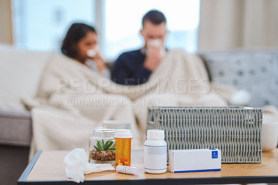 Buy stock photo Cropped shot of an unrecognizable couple sitting on the sofa at home together and feeling sick