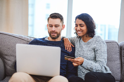 Buy stock photo Cropped shot of a happy young couple sitting on the sofa together and using a laptop for online shopping