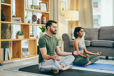 Buy stock photo Shot of a young couple meditating together at home
