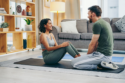 Buy stock photo Shot of a young couple exercising together at home