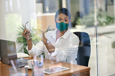 Buy stock photo Shot of a mature businesswoman wearing a mask while working in an office