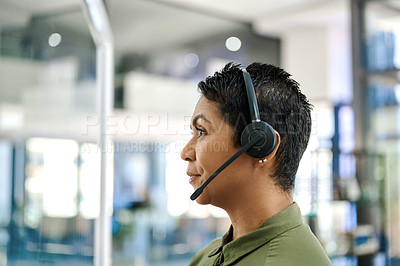 Buy stock photo Shot of a mature businesswoman wearing a headset in an office