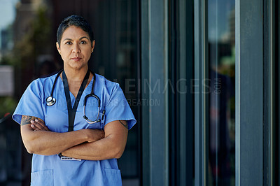 Buy stock photo Portrait of a mature doctor standing with her arms crossed outside a hospital