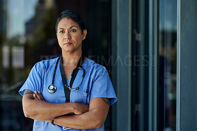 Buy stock photo Shot of a mature doctor standing with her arms crossed outside a hospital