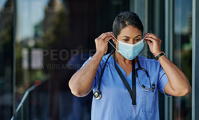 Buy stock photo Shot of a mature doctor putting on a mask while standing outside a hospital