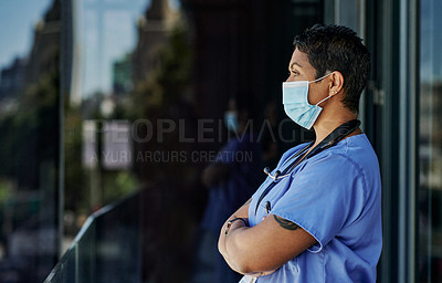 Buy stock photo Shot of a mature doctor wearing a mask while standing outside a hospital
