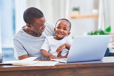 Buy stock photo Shot of a young man using a laptop with his baby son sitting on his lap at home
