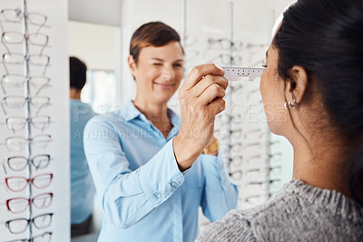 Buy stock photo Shot of an optometrist examining her patient's eyes with a pd ruler