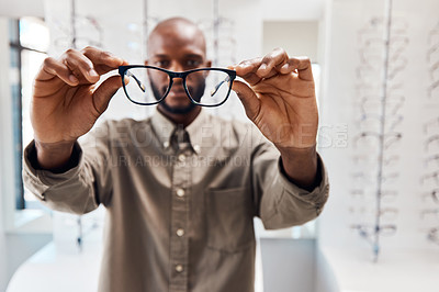 Buy stock photo Shot of a young woman buying a new pair of glasses at an optometrist store
