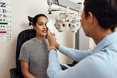 Buy stock photo Shot of an optometrist covering her patient's eyes with an occluder during an eye exam