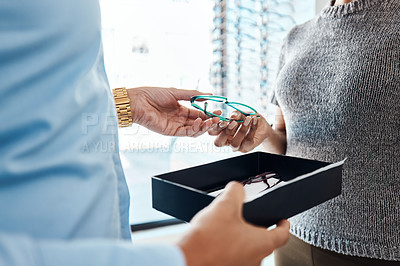 Buy stock photo Shot of a an optometrist helping a woman choose a new pair of glasses