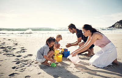 Buy stock photo Shot of a couple helping their two kids while building sandcastles on the beach